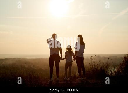 Silhouette of a family - father, mother and daughter standing on the hill with their backs to the camera and looking to the horizon on the sunset