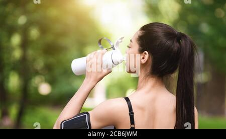 Healthy Lifestyle Concept. Asian jogger girl drinking water, resting after running outdoors