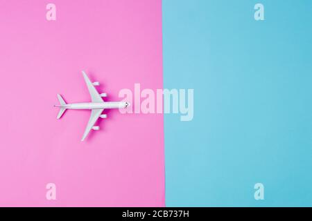 Flat lay of miniature toy airplane on Pink and yellow background - Stock Photo
