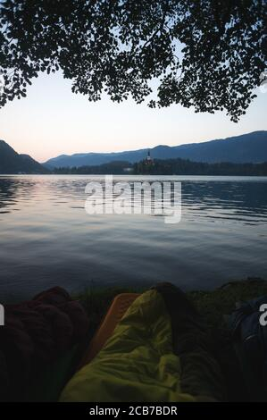 Early morning lake Bled in Slovenia. Calm lake, rising sun behind the mountains, Alps. Sleeping bags in the foreground, Outdoor Adventure in the Trigl - Stock Photo