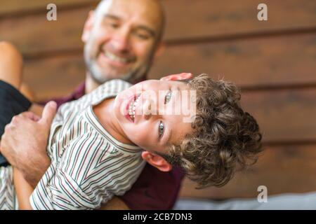 Hispanic father sitting and hugging his son.