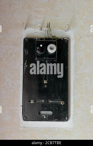 Very old black electrical fuses box hanging on white rural wall with copy space - Stock Photo