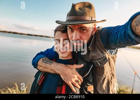 Father hugs son and takes selfie. They have fun. Background lake.