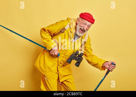 old crazy funny man walking with poles, lifestyle, close up photo. free time, spare time, isolated yellow bacakground, man keeps fit