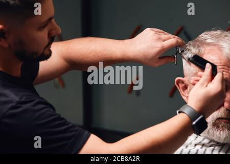 young talented barber doing new modern hairstyle for client. barber preparing old man for a date, party , event
