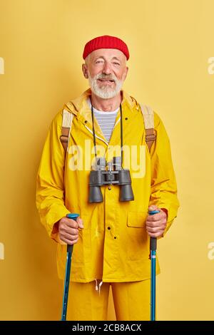old tourist with binocular in stylish coat takes care of health, wellness, fitness, treatment. close up photo. isolated yellow background