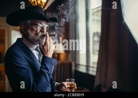 Elegant senior gentleman wearing spectacles and grey-haired beard standing at pub in wide-brimmed hat with glass of alcohol drink and cigar. Elderly m