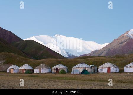 Osh, Kyrgyzstan - Morning Sunlight Landscape of Lenin Peak (7134m) at Tourist Yurt camp of Tulpar Kol Lake in Alay Valley, Osh, Kyrgyzsta - Stock Photo