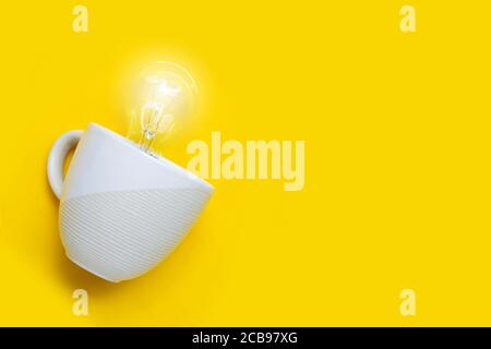 Light bulb in white cup on yellow background. Ideas and creative thinking concept. Copy space