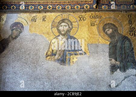 The Deësis mosaic, ancient Christian art showing Christ, Virgin Mary and John the Baptist, on the upper gallery inside Hagia Sophia. Istanbul. Turkey. - Stock Photo