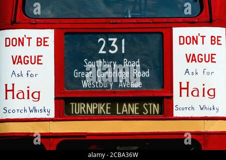 Woodcote, Oxfordshire, United Kingdom: 'Don't Be Vague Ask For Haig', one of the most famous and long-running slogans in Scotch Whisky advertising, hand-painted on both top deck panels on the front of JXN 325, a preserved London Transport Routemaster (RT 935) double-decker bus on display at the 50th Anniversary Woodcote Steam and Vintage Transport Rally in July 2013.  The AEC Regent III bus, built in 1949 with Park Royal bodywork, was retired from service in the early 1960s and was bought for preservation in 1971.  It has since appeared regularly at classic and vintage vehicle rallies and show - Stock Photo