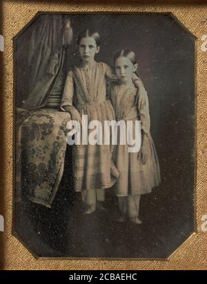Two Identically Dressed Young Girls Standing Next to a Table, 1840s. - Stock Photo