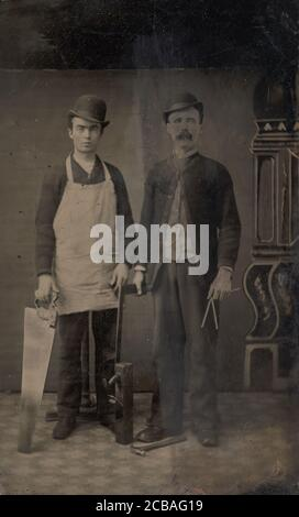 Two Carpenters with a Handsaw, Wood Plane, Hammer, Compass, and Square, 1880s. - Stock Photo