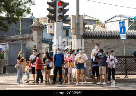 Beijing, China. 12th Aug, 2020. People wait at a pedestrian crossing in central Beijing. Credit: Artyom Ivanov/TASS/Alamy Live News - Stock Photo