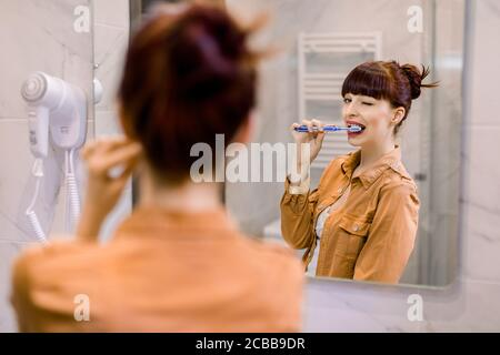 Horizontal shot of young red haired smiling woman having fun in bathroom, winking to the mirror, brushing teeth and enjoying morning hygiene