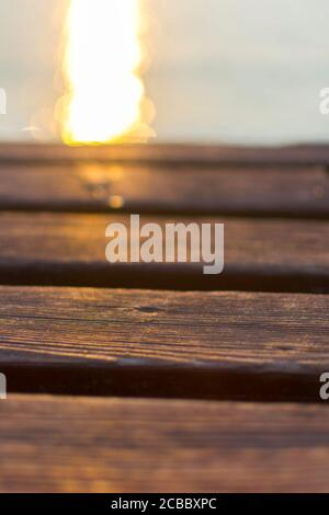 Wooden deck of a jetty in Lake Garda. The sun is reflected in the water. The wood is warm, brown in color.