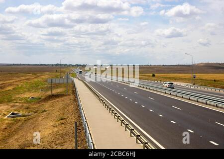 highway in steppe against a blue sky,long road stretching out into the distance.
