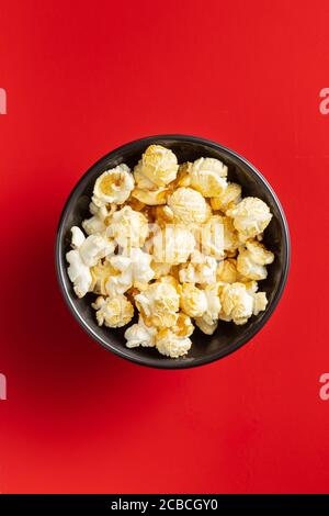 Sweet tasty popcorn in bowl on red background. Top view.