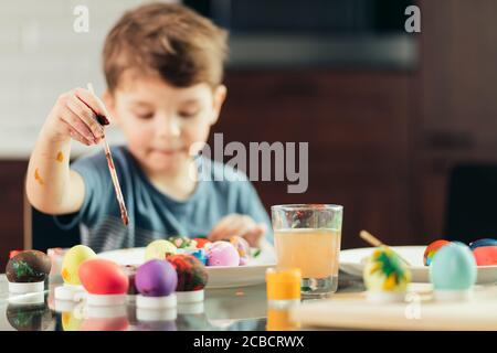 4-year old caucasian boy helps his mother with preparations to Easter. Concentrated kid is engaged in creative activity, painting out Easter eggs. chi