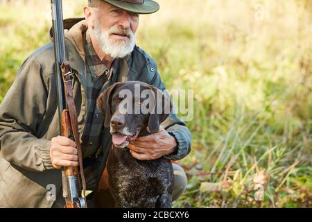 Senior man hug his hunter dog in autumn forest. Man wearing casual hunting clothes, sitting on ground.Gun in hands - Stock Photo