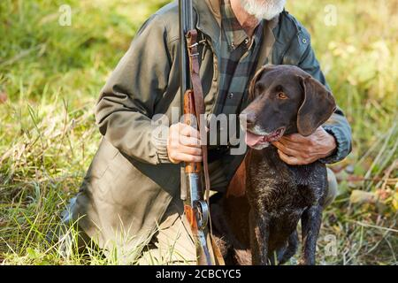 Cropped man with beard hug his hunter dog in autumn forest. Man wearing casual hunting clothes, sitting on ground.Gun in hands - Stock Photo