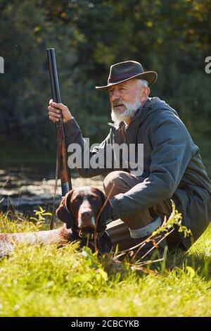 Senior good-looking hunter with his tracker dog in hunt on wild ducks. Sitting near lake, wearing hat, holding gun - Stock Photo