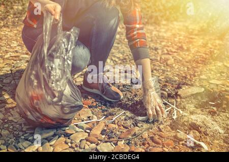 The volunteer is removed in the forest after a season of picnics and barbecues. Woman collects plastic forks on the old fire pit. Earth day and enviro - Stock Photo