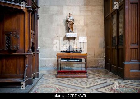 A small, quiet statue on the wall in front of prayer candles in a side alcove at the Votivkirche, Votive church. In Vienna, Austria. - Stock Photo