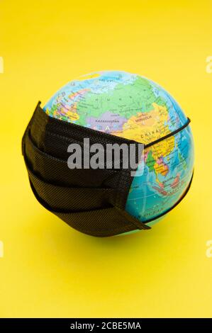 Terrestrial globe model with black surgical mask isolated on yellow background. Concept: Planet Earth in protection against Coronavirus (COVID-19). - Stock Photo