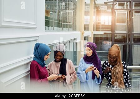 Islamic female travel blogger sharing info from smartphone with her followers while standing in group of four in hotel lobby