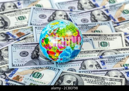Earth globe in one hundred dollar banknote. International business Global Economy crisis Concept. - Stock Photo