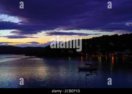 Beautiful purple, orange, red and blue sunset over Poros Island, Greece. Poros is a small Greek island-pair in the southern part of the Saronic Gulf, - Stock Photo