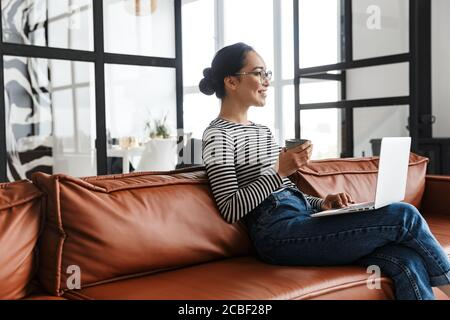 Attractive smiling young asian woman wearing casual clothes relaxing on a leather couch at home, working on laptop computer - Stock Photo