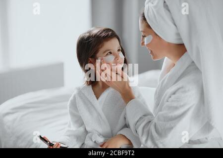 beauty concept. careful attentive mother use patches for eyes and her daughter in mask too. parents and children interested in beauty procedures