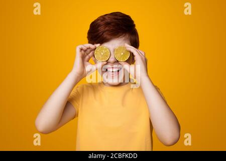 Happy ginger boy covering his eyes with lemons and smile on a yellow studio wall