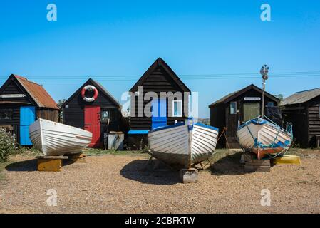 Suffolk coast UK, view in summer of fishing boats and fishermen's huts sited on the beach in Southwold harbour, Suffolk, England, UK
