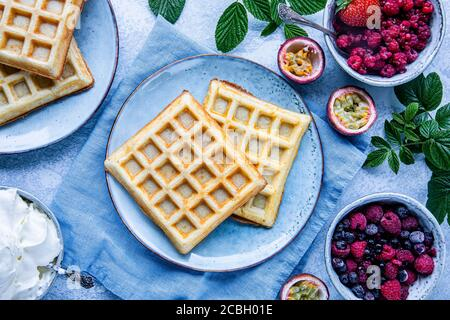 Belgian waffles with raspberries, blueberries and passion fruit. There is a bowl of whipped cream on the table. The food is seen from above, flat lay - Stock Photo