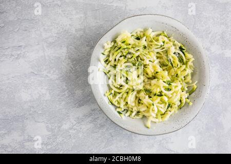 Zucchini spaghetti or noodles (zoodles) in a bowl with gray background Top view overhead with copy space room for text. - Stock Photo