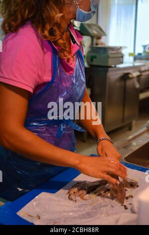 Italy - August 2020 at the fish market butcher works cleaning and preparing fish