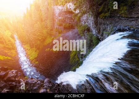 Beautiful View of a Waterfall rushing down in a rocky canyon - Stock Photo