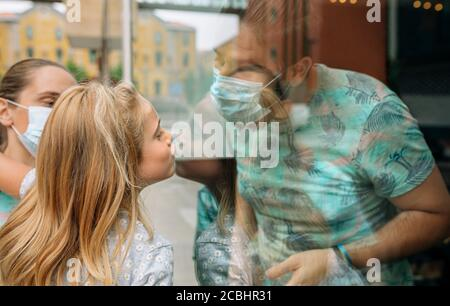 Girl giving a kiss through the glass to her father