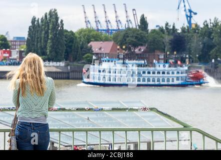 Hamburg, Germany - June 8, 2020: A young blonde woman stands at a railing of the Landungsbruecken. She looks at the ships in the harbor. A paddle stea Stock Photo