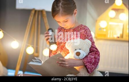 Cute little girl reading book with flashlight in illuminated room - Stock Photo