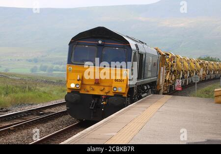 Class 66 diesel electric train in Direct Rail Services livery approaching Ribblehead station on Settle to Carlisle railway line on 12th August 2020. - Stock Photo