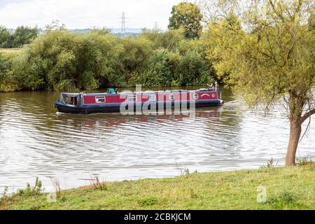 A barge or longboat cruising on the River Severn at Wainlode, Gloucestershire UK - Stock Photo
