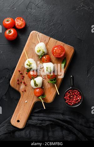 caprese salad skewer with tomato on sticks Italian traditional caprese salad ingredients. Mediterranean food. over black stone background overhead