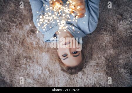 A young blonde girl in sweater holding garlands in hands lying on carpet, Merry Christmas and Happy New Year - Stock Photo
