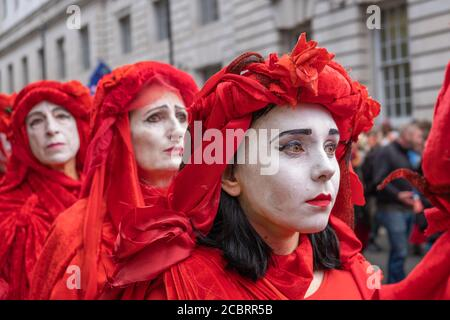 London, UK - October 18, 2019: A row of Extinction Rebellion Red Brigade protesters parading in London - Stock Photo