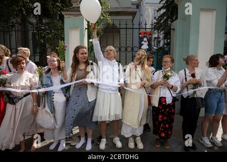 Moscow, Russia. 15th of August, 2020 Women hold flowers as people, some of them ethnic Belarusians and white clothes, gather for a rally against the results of the Belarusian presidential election in front of Belarusian Embassy in Moscow, Russia. About 400 people, mostly women, line up with flowers along Maroseyka street near Belarusian Embassy in solidarity with protesters injured in the latest rallies in Belarus - Stock Photo