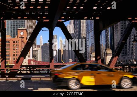 yellow car moving across a bridge with Chicago city center  in background - Stock Photo
